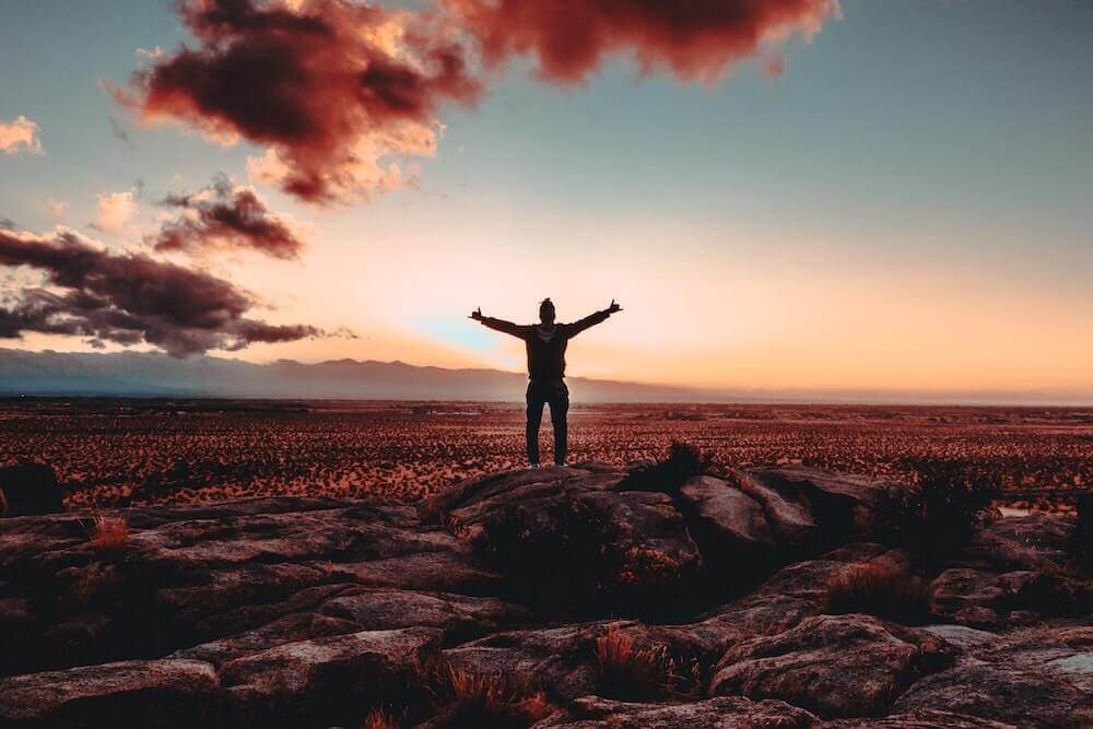 person with arms outstretched in front of sunset